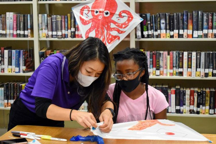 """Sari Sugai, left, Camp Zama Army Community Service Exceptional Family Member Program and New Parent Support Program coordinator, helps Alyssa Turner, 12, make a kite during a """"Fun Friday"""" event at the Sagamihara Family Housing Area Library, SFHA, Japan, May 28. (Photo Credit: Winifred Brown)"""