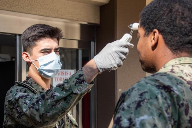A hospital corpsman checks the temperature of a sailor visiting a health clinic at Naval Air Facility Atsugi, March 26, 2020. RAFAEL AVELAR/U.S. NAVY