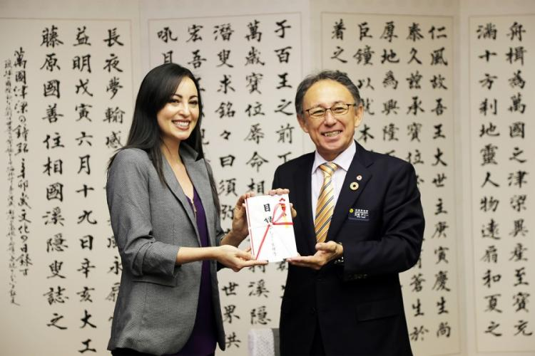 Marine Corps spouse Mari Gregory presents Okinawa Gov. Denny Tamaki with more than $11,000 in donations for the restoration of Shuri Castle, Thursday, Feb. 6, 2020. The popular cultural landmark was devastated by fire in October. AYA ICHIHASHI/STARS AND STRIPES