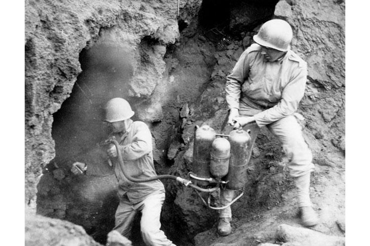 Capt. James T. Kolb of Company A, 147th Infantry, assisted by Sgt. Keogh, uses a flamethrower against dug-in Japanese troops on Iwo Jima, April 20, 1945. Relieving Marine Corps units, the Soldiers of the Ohio National Guard's 147th Infantry Regiment fought on the island from March to September 1945, clearing the remaining enemy troops, some of whom were hiding in intricate cave systems. (Photo from Ohio Army National Guard Historical Collections)