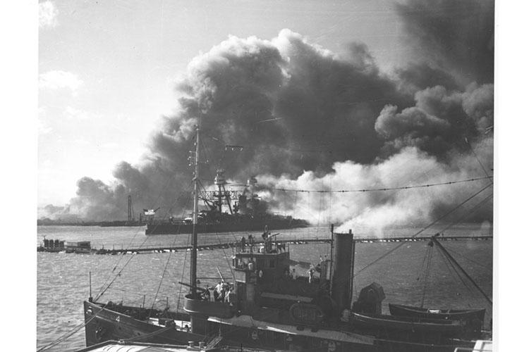 The USS Nevada (BB36) after the Japanese attack on Pearl Harbor, Dec. 7 1941. Moving to position away from enflamed ships. Foreground salvage and rescue tugs gun crews in action. Photo courtesy of the U.S. National Archives and Records Administration.