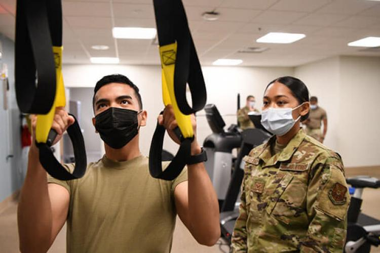 Senior Airman May Cortez, physical therapy technician, assists Airman 1st Class Kyle Maglalang, medical materiel technician, while performing a row on the Total Body Resistance Exercise Training machine, June 24, 2021, in the Medical Clinic at F.E. Warren Air Force Base, Wyoming. The TRX is used for upper body strengthening and stability (Photo by: U.S. Air Force Airman 1st Class Faith Iris MacIlvaine).