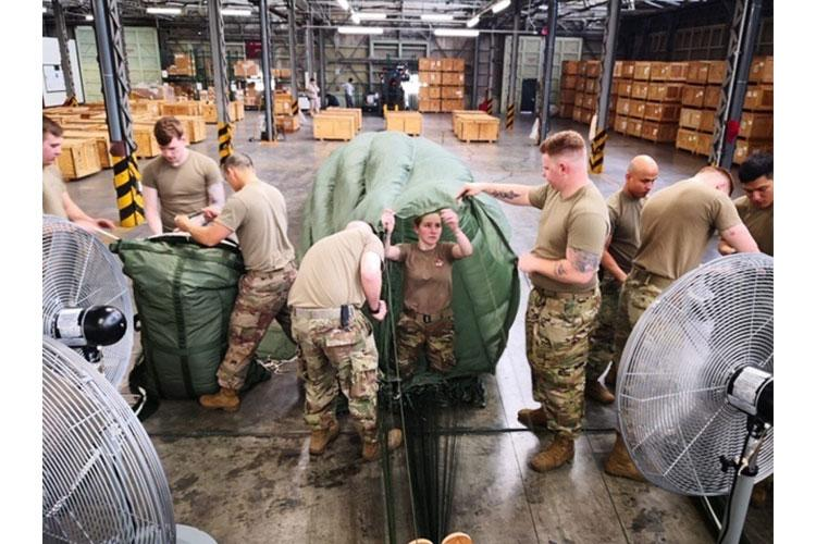 Parachute Riggers from the 4th Quartermaster Theater Aerial Delivery Company, pack G-11 Cargo Parachute systems for the Army Preposition Stocks-4 Aerial Delivery Operational Projects. (Photo by Chief Warrant Officer 2 Mervin Terre, 4th QM Co.)