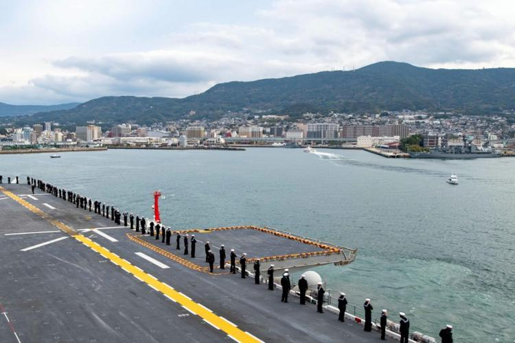 Sailors man the rails as the amphibious assault ship USS America arrives in Sasebo, Japan, Dec. 6, 2019. VINCENT ZLINE/U.S. NAVY