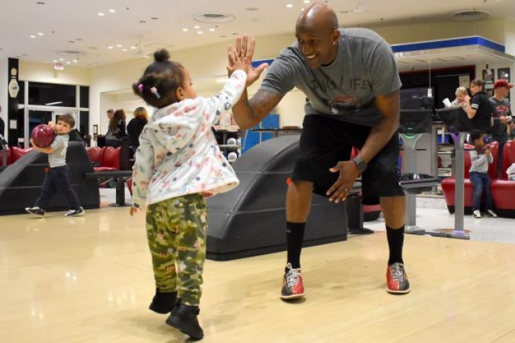 "Sgt. 1st Class Jamar Alford, a Soldier assigned to U.S. Army Japan, gives his daughter, Kayja, 2, a high five during the ""Bowl With the Bunny"" event April 17. Since April is National Autism Awareness Month and National Child Abuse Prevention Month, Camp Zama Army Community Service got together with the bowling alley to provide information about both issues during the event. (Photo Credit: Wendy Brown, U.S. Army Garrison Japan Public Affairs)"