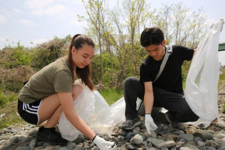Nina Sakamoto-Flack, a Camp Zama volunteer, and Kazuki Chigono, a volunteer from the Hiratsuka Agricultural High School, help clean garbage during a U.S. Army Garrison Japan-sponsored Earth Day event in Zama City on April 21, 2019. (Photo Credit: Timothy Flack, U.S. Army Garrison Japan Public Affairs)