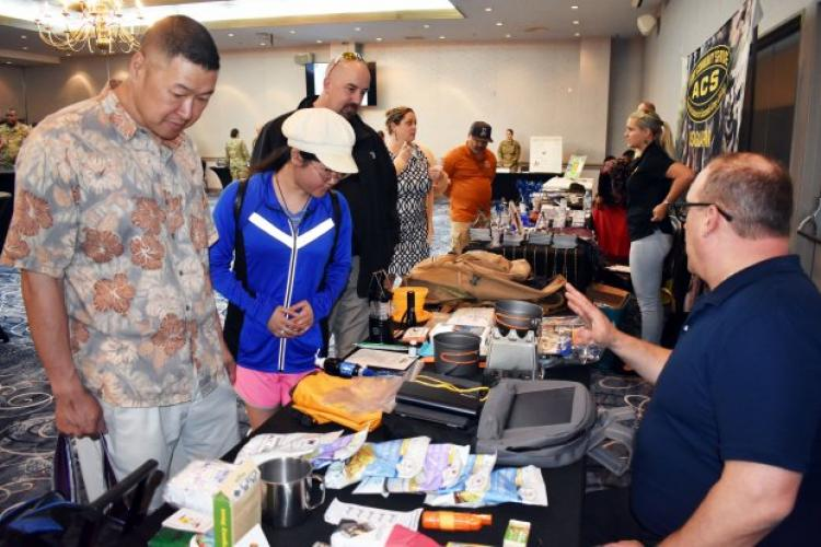 From left, Brian Lim, his daughter Celine Lim and David Carlile look over emergency kits during the emergency preparedness Community Information Exchange at the Camp Zama Community Club May 10. Mike Dahle, right, an occupational safety and health specialist for U.S. Army Garrison Japan, displayed two of his personal kits as examples. (Photo Credit: Wendy Brown, U.S. Army Garrison Japan Public Affairs)