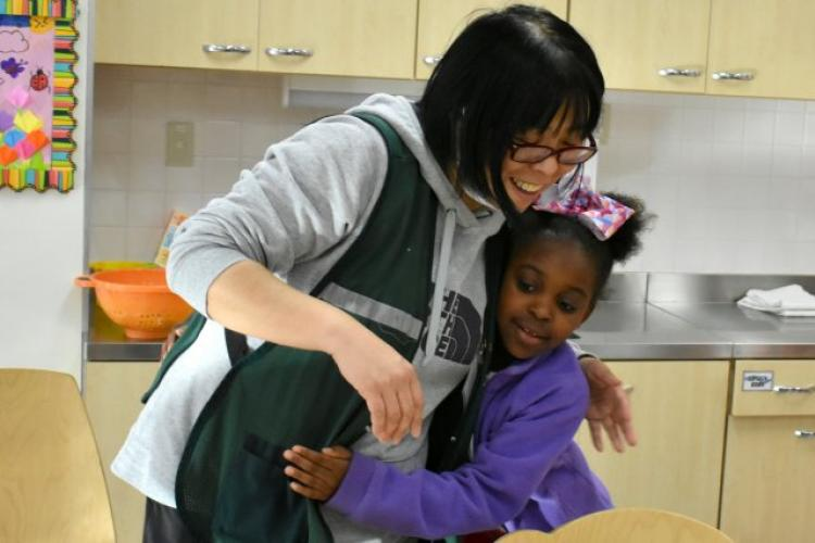 Ariana Inniss, 8, hugs Marino Nakanowatari, a caregiver in the art room, at the Camp Zama Student Activity Center Feb. 22. (Photo Credit: Photo by Wendy Brown, U.S. Army Garrison Japan Public Affairs)