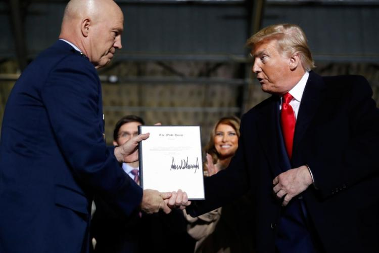 President Donald Trump shakes hands with Gen. Jay Raymond, after signing the letter of his appointment as the chief of space operations for U.S. Space Command during a signing ceremony for the National Defense Authorization Act for Fiscal Year 2020 at Andrews Air Force Base, Md., Friday, Dec. 20, 2019. ANDREW HARNIK/AP