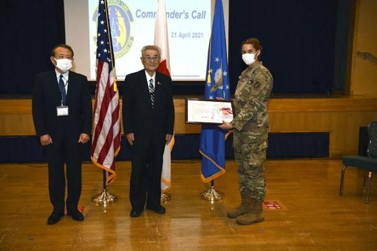 """City of Misawa officials, Director of Okamisawa """"Jido-kan"""", or after school program, Norio Yamamoto and Social Welfare President, Shinji Kuroda, present a letter of appreciation to U.S. Air Force Senior Airman Hannah Tatum, 35th Communication Squadron radio frequency transmission systems technician, during an all-call on Misawa Air Base, April 21, 2021. Tatum has been a part of Jido-kan since she arrived to Misawa in 2018. (U.S. Air Force photo by Airman 1st Class Joao Marcus Costa)"""