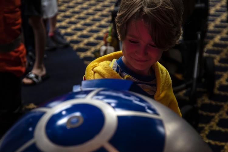 "A child investigates a replica of R2-D2 from ""Stars Wars"" during the inaugural Yokota-Con at Yokota Air Base, Japan, Saturday, Oct. 19, 2019. THERON GODBOLD/STARS AND STRIPES"