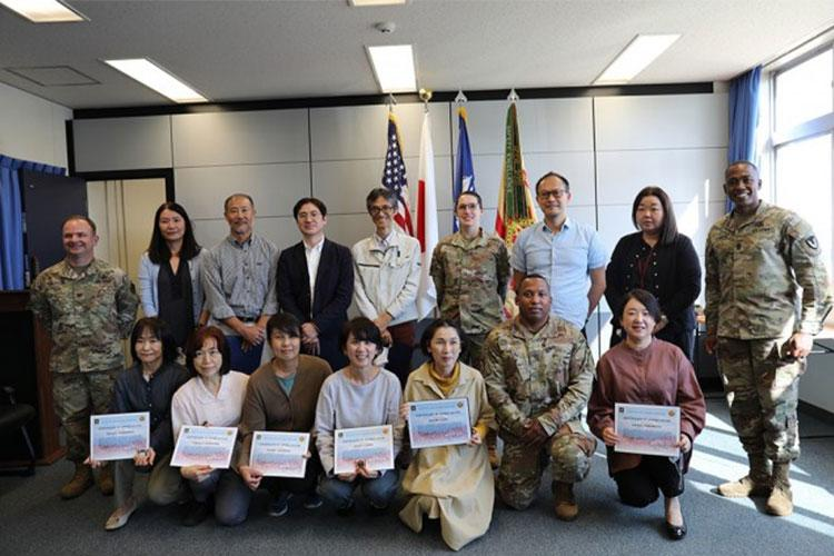 U.S. Army Garrison Japan Commander Col. Christopher Tomlinson, left, and USAG Japan Command Sgt. Maj. Justin Turner, right, pose for a group photo with members of the Air Force's 374th Contracting Squadron team Oct. 14 at Yokota Air Base, Japan, following an award ceremony where USAG Japan recognized the 374th CONS for their support with a USAG Japan budgetary mission. (Noriko Kudo)