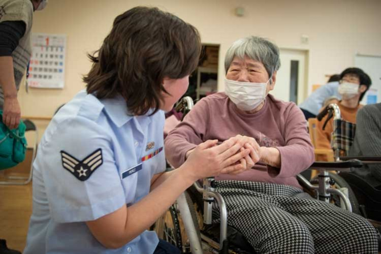 Senior Airman Patricia Perez, United States Air Force Band of the Pacific popular music ensemble Pacific Trends bassist, connects with a concert attendee immediately following the show at the Musashimurayama En nursing home in Musashimurayama, Tokyo, Japan, Jan. 25, 2019. (U.S. Air Force photo by Senior Airman Matthew Gilmore)