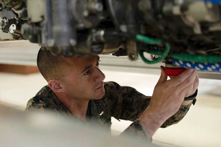 First Lt. Simon Miller of Marine Aviation Logistics Squadron 12 at Marine Corps Air Station Iwakuni, Japan, demonstrates the installation of drain plugs that are part of an engine ship kit he designed and built using a 3D printer, Nov. 29, 2018. (JAMES BOLINGER/STARS AND STRIPES)