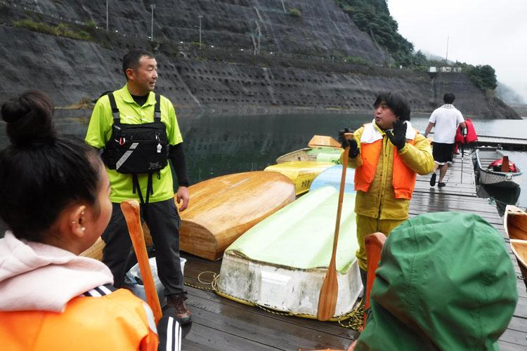 Yoshi Nakamura, 374th Force Support Squadron outdoor recreation tour guide, left, and a Naguri Canoe Atelier member give a safety briefing to Yokota Air Base members before canoeing near the Arima Dam, Saitama Prefecture, Japan, Oct. 14, 2017. They showed personnel the basics of how to properly use a canoe. (U.S. Air Force photo by Staff Sgt. David Owsianka)