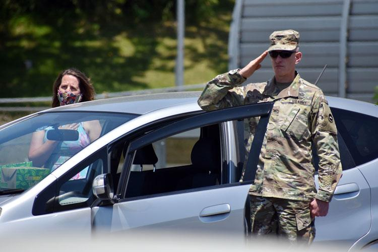 Col. Cory Delger salutes during the national anthem during a drive-in National Day of Prayer observance at Camp Zama, Japan, May 14. His wife, Candice Wallis-Delger, stands left. (Photo Credit: Winifred Brown)