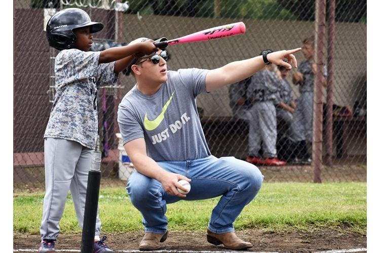 Steven Padgett, right, acting coach of the Camp Zama T-ball team, and Kaiden Pollard, a player, discuss batting during a game at Camp Zama May 18. (Photo Credit: Wendy Brown, U.S. Army Garrison Japan Public Affairs)