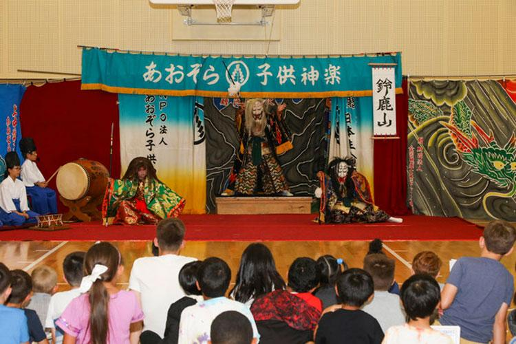 Children with the School Age Center attend a Kagura dance performance at Marine Corps Air Station (MCAS) Iwakuni, Japan, July 15, 2019. The Aozora Kids Kagura Association, based out of Hiroshima City, visited MCAS Iwakuni to give Japanese and American children a way to interact with each other and to show the American children a piece of traditional Japanese culture. This was the 3rd annual visit the association has made to MCAS Iwakuni. (U.S. Marine Corps photo by Cpl. Stephen Campbell)