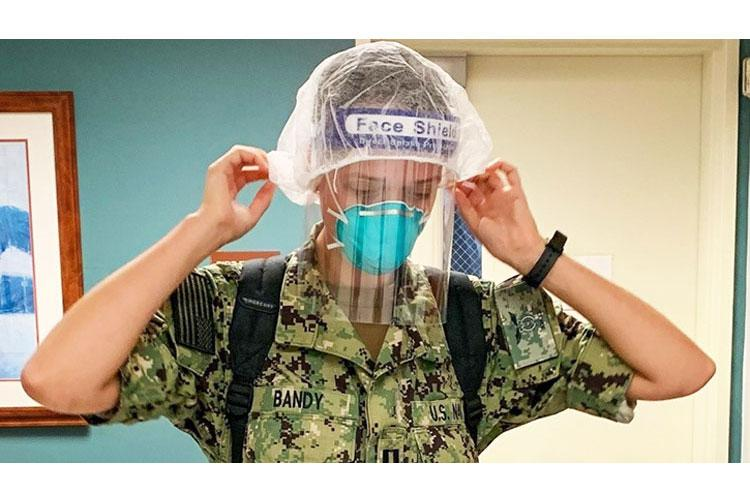 Navy Lt. Tess Bandy, a nurse from Naval Medical Center, Camp Lejeune, N.C. assigned to the U.S. Navy Acute Care Team, dons personal protective equipment in preparation for one-on-one training with hospital staff caring for patients in an Enhanced Precaution Unit at Valley Baptist Medical Center- Harlingen in Harlingen, Texas. (Photo by Army Maj. Bonnie Conard, U.S. Army - North.)