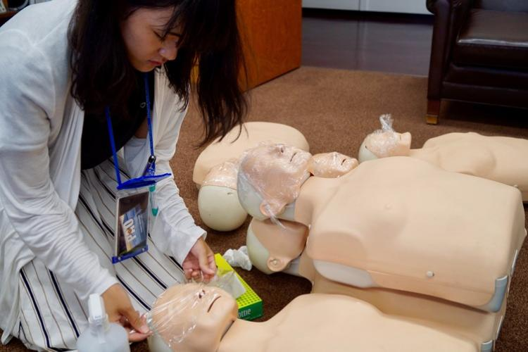 Ai Masuda, a college student assigned to the U.S. Army Garrison Japan Safety Office as part of USAG Japan's summer internship program, sanitizes and puts plastic wrap on CPR dummies Aug. 9 after a class on how to use an automated external defibrillator, or AED. Masuda and 16 other students are taking part in the four-week program and were assigned to nine different garrison organizations. (Photo Credit: Kimberly Lopes, U.S. Army Garrison Japan Public Affairs)