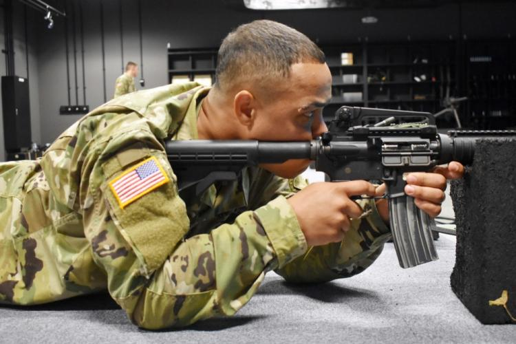 Sgt. Cameron Stine, assigned to Headquarters and Headquarters Battery, 38th Air Defense Artillery Brigade, shoots a virtual M4 at the Engagement Skills Trainer during the brigade's Soldier and noncommissioned officer of the quarter competition at Sagami General Depot, Japan, Sept. 5, 2019.