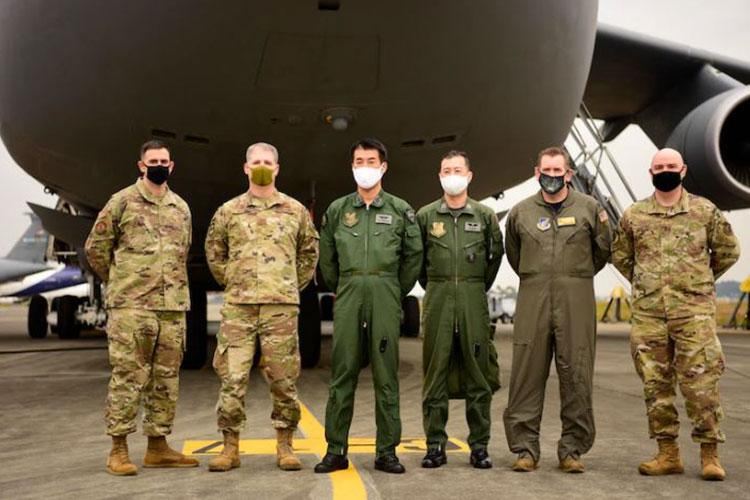 U.S. Air Force and Japan Air Self-Defense Force officers and senior non-commissioned officers pose in front of the nose of the C-5M Super Galaxy on Yokota Air Base, Japan, Nov. 6, 2020. There were opportunities for JASDF leadership to tour the cockpit, cargo deck, and learn more about the aircraft's capabilities.