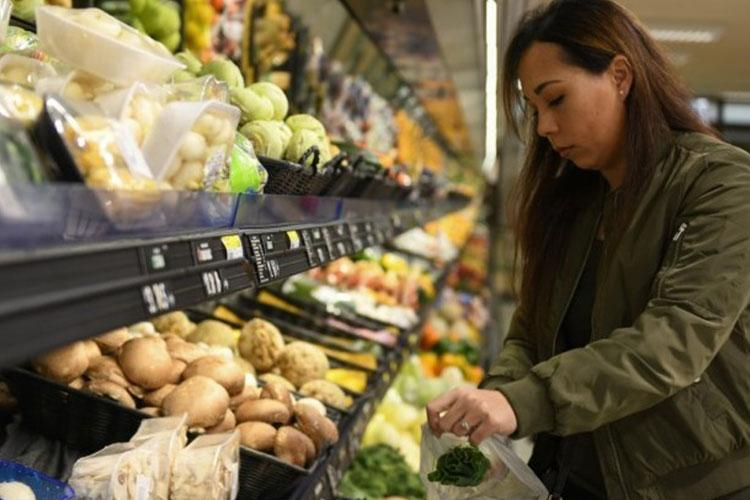 U.S. Air Force Senior Airman Sherraye Carter, 606th Air Control Squadron unit deployment manager, bags produce at the commissary on Aviano Air Base, Italy, March 30. Carter volunteered to help pick up and deliver groceries to people who can't get them themselves. (Air Force photo: Airman 1st Class Ericka A. Woolever)