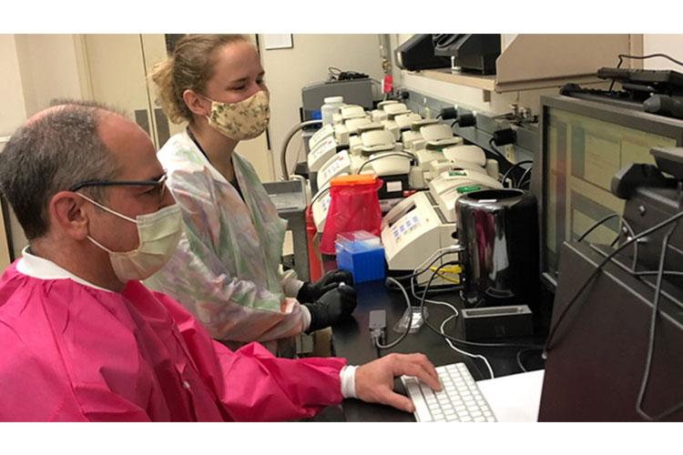 Research associate Lindsay Glang and senior bioinformatics analyst Gregory Rice sequencing SARS-CoV-2 genomes on Oxford Nanopore MinION platform at NMRC BDRD. (Photo Courtesy of Naval Medical Research Center, Genomics & Bioinformatics Department.)