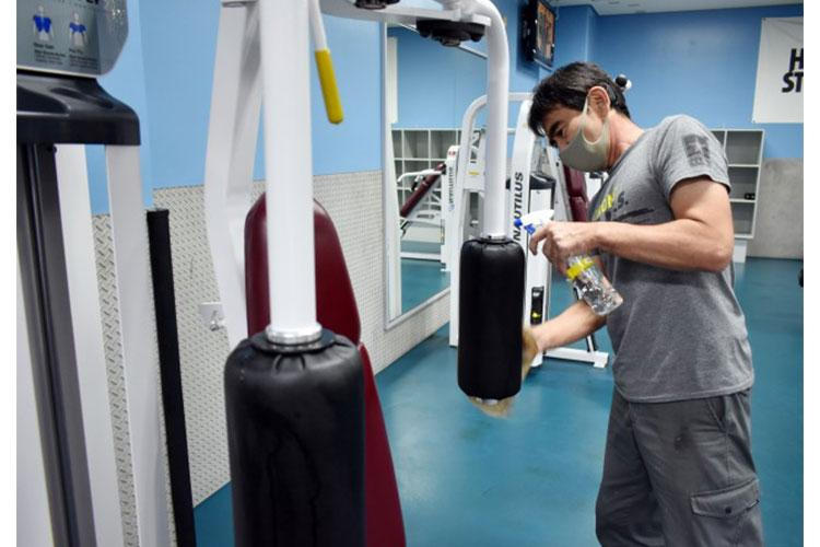 """Hiroto """"ET"""" Mizukabo cleans a machine in the weight room at the Yano Fitness Center at Camp Zama, Japan, Aug. 27. (Photo Credit: Winifred Brown)"""