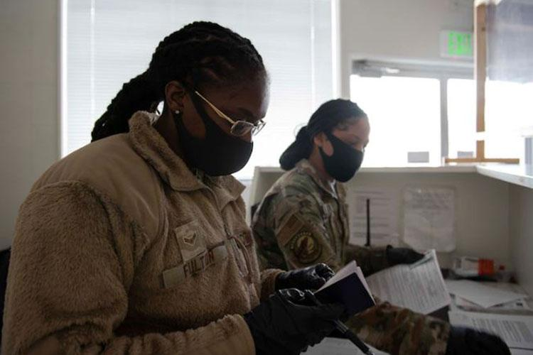 Airman 1st Class Kimarri Fulton and Airman 1st Class Renee Rora, 374th Security Forces Squadron customs immigration inspectors, inspect traveler documents for incoming personnel, March 3, 2021, at Yokota Air Base, Japan. New hairstyle options have expanded from traditional buns to braids, ponytails and some styles in between (U.S. Air Force photo by Senior Airman Hannah Bean)
