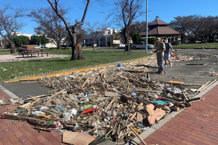 Workers assess debris from Typhoon Hagibis that collected along the water's edge at Yokosuka Naval Base, Japan, Sunday, Oct. 13, 2019. CAITLIN DOORNBOS/STARS AND STRIPES