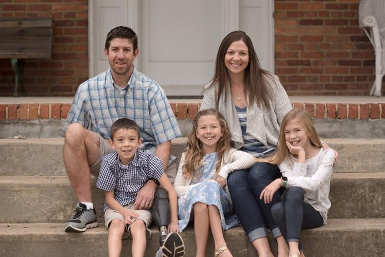 Retired Army Capt. Ryan Kules with his wife Nancy and their children Jillian, Liv and Evan. Injured by a roadside bomb in 2005, Kules lost his right arm above the elbow and his left leg above the knee. He now works with Wounded Warrior Project and helped push for new legislation to get more government funding for disabled veterans to modify their homes. PHOTO COURTESY RYAN KULES.