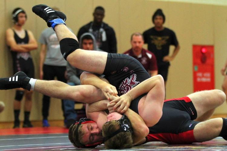 Nile C. Kinnick's Ethan Hamilton locks in a cradle on Matthew C. Perry's Parker Staley at 148 pounds during Saturday's DODEA-Japan dual meet tournament. Hamilton pinned Staley and the Red Devils won the dual meet 37-15. SHION RUDOLPH/SPECIAL TO STRIPES