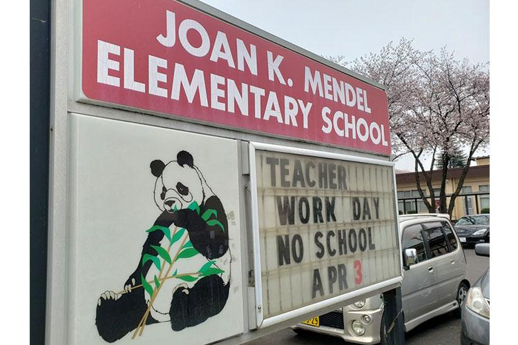 A sign outside Joan K. Mendel Elementary School announces an upcoming teacher work day at Yokota Air Base, Japan, Tuesday, March 31, 2020. THERON GODBOLD/STARS AND STRIPES
