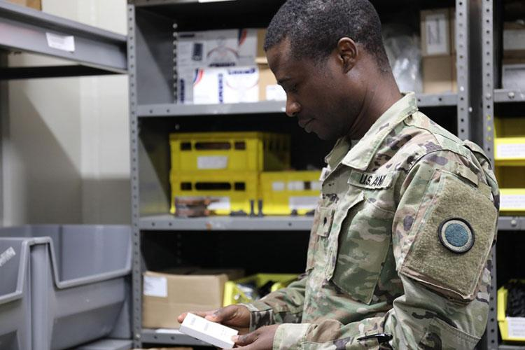 """Spc. Joseph Ngwa, assigned to I Corps (Forward) at Camp Zama, Japan, conducts an inventory May 8 in in the Transportation Motor Pool's supply room. In April, Ngwa learned his mother, Jeannette, who lives in France, had contracted the coronavirus. He spent the next week experiencing an """"emotional battle"""" while he waited for an update on her condition. Jeannette ultimately recovered from her illness."""