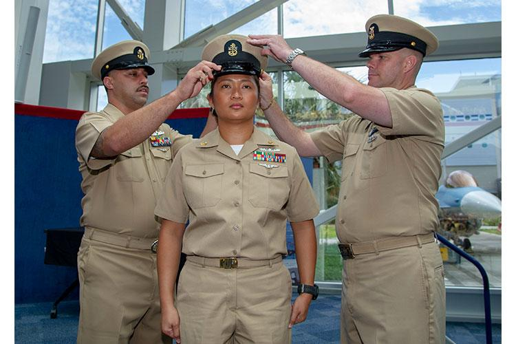 PENSACOLA, Fla. (Sept. 13, 2019) Chief Hospital Corpsman Joyce Layug, assigned to Naval Hospital Pensacola (NHP), is capped by fellow chiefs during a chief petty officer pinning ceremony at the National Naval Aviation Museum. Among those pinned, four Chiefs are assigned to NHP. (U.S. Navy photo by Mass Communication Specialist 3rd Class Carter Denton/Released)