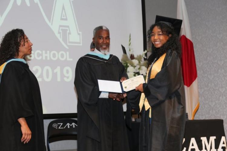 Matrika Franklin, the salutatorian for the Zama American High School graduating class of 2019, receives her diploma from ZAHS Principal Wayne Carter during the commencement ceremony June 6 at the Camp Zama Community Club. (Photo Credit: Noriko Kudo, U.S. Army Garrison Japan Public Affairs)