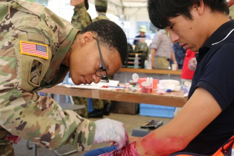 Staff Sgt. Karim Acosta, left, and Sgt. 1st Class Tatiana Mason, left, assigned to U.S. Army Medical Department Activity--Japan, pause for a photo with a young volunteer role-player after putting special-effects makeup on his arm during the annual Zama City disaster drill, held Sept. 7 at Zama Elementary School near Camp Zama, Japan. (Photo Credit: Noriko Kudo, U.S. Army Garrison Japan Public Affairs)