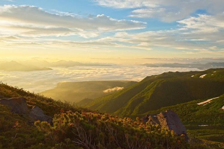 The golden light of the sunrise light up the cloud covered valley. Photo: Sandro Bernardinello