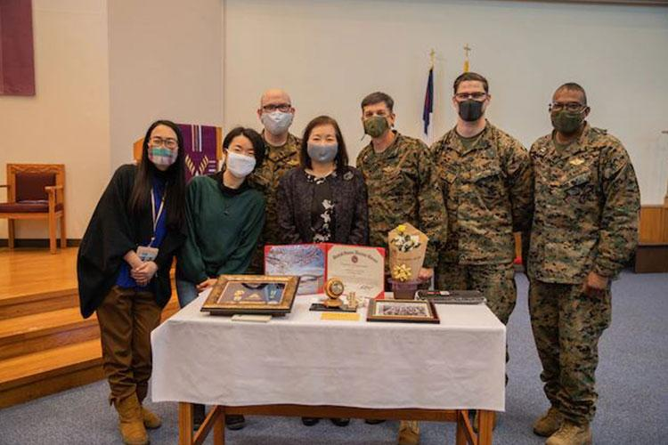 Noriko Yamada, center, an administrative specialist with the station chapel, stands among her co-workers and friends during her retirement ceremony held aboard Marine Corps Air Station Iwakuni, Japan, Feb. 19, 2021. Yamada retired after working for more than 40 years as an administrative specialist. (U.S. Marine Corps photo by Lance Cpl. Trista Whited)