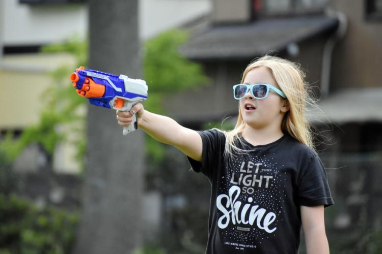 Rivers Prokopi, 11, takes aim at a dinosaur target with her toy dart gun while participating in the Jurassic SHA Nerf Dinosaur Hunt at the Sagamihara Family Housing Area, Japan, June 2.