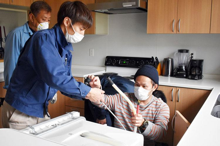 Members of the U.S. Army Garrison Japan maintenance team replace a dishwasher in a housing unit at Sagamihara Family Housing Area, Japan, April 21.