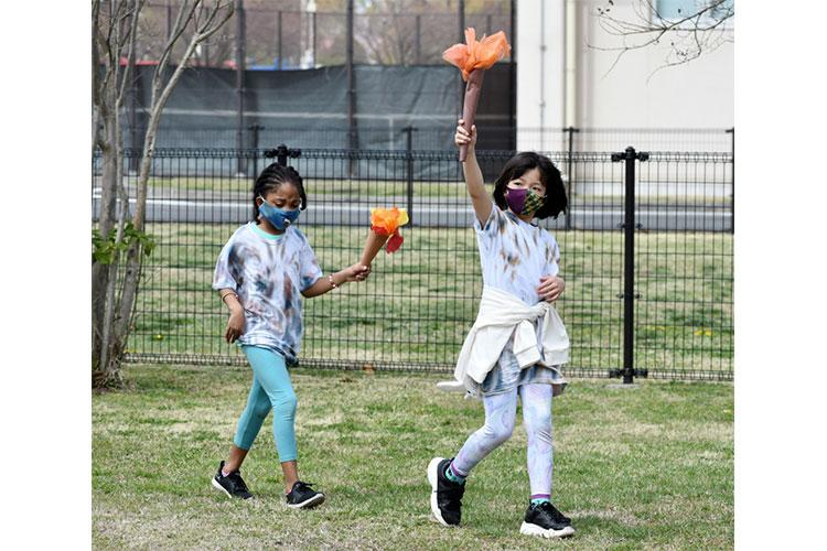Emma Owen, right, and Cymone Vaughn, second-graders, participate in the opening ceremony of the 2021 School Age Center Olympics at Sagamihara Family Housing Area, Japan, April 1.