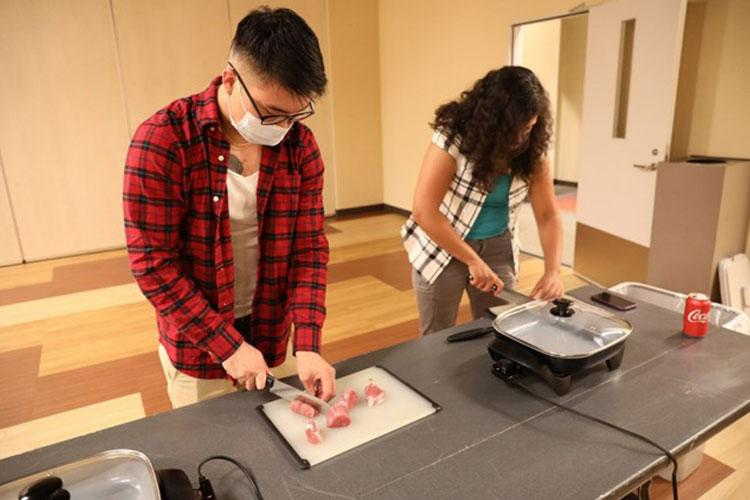 Spc. Joshua Yi, left, and Capt. Graciela Orantes slice pork tenderloin during a free cooking class Sept. 2 at the Better Opportunities for Single Soldiers Warrior Zone at Camp Zama, Japan. Volunteer instructors in the community offer the class regularly to members of the BOSS program as part of a life-skills curriculum. The Soldiers also learn things like the use and maintenance of kitchen equipment and utensils, and basic kitchen safety. (Photo Credit: U.S. Army)